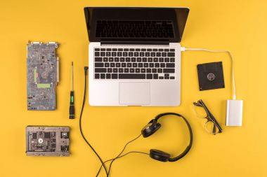 top view of laptop with headphones, eyeglasses and tools on yellow