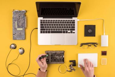 cropped shot of person fixing laptop on yellow