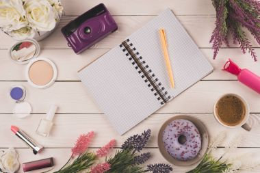 top view of empty open notebook with pen, camera, flowers, cosmetics and cup of coffee with doughnut on table top