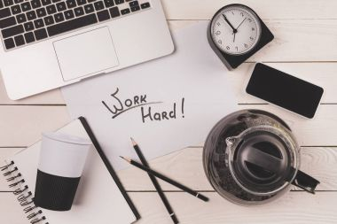 laptop, coffee pot, paper cup, clock, smartphone and inscription work hard at workplace