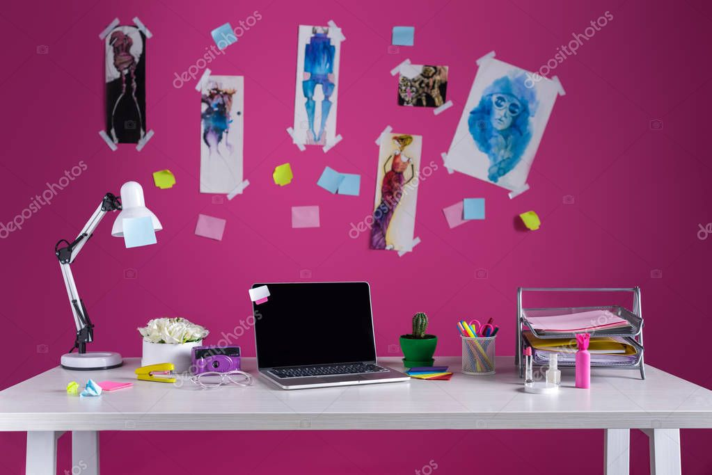 laptop with blank screen and office supplies at fashion designer workplace