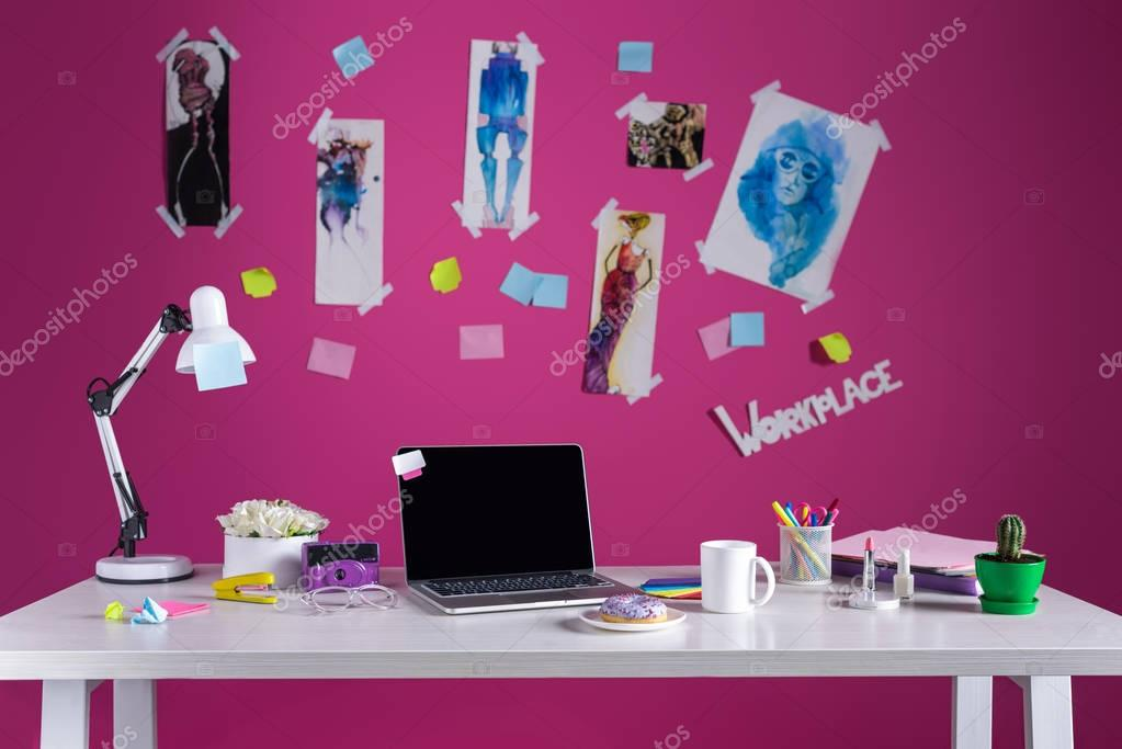 fashion designer workplace with sketches and laptop on table