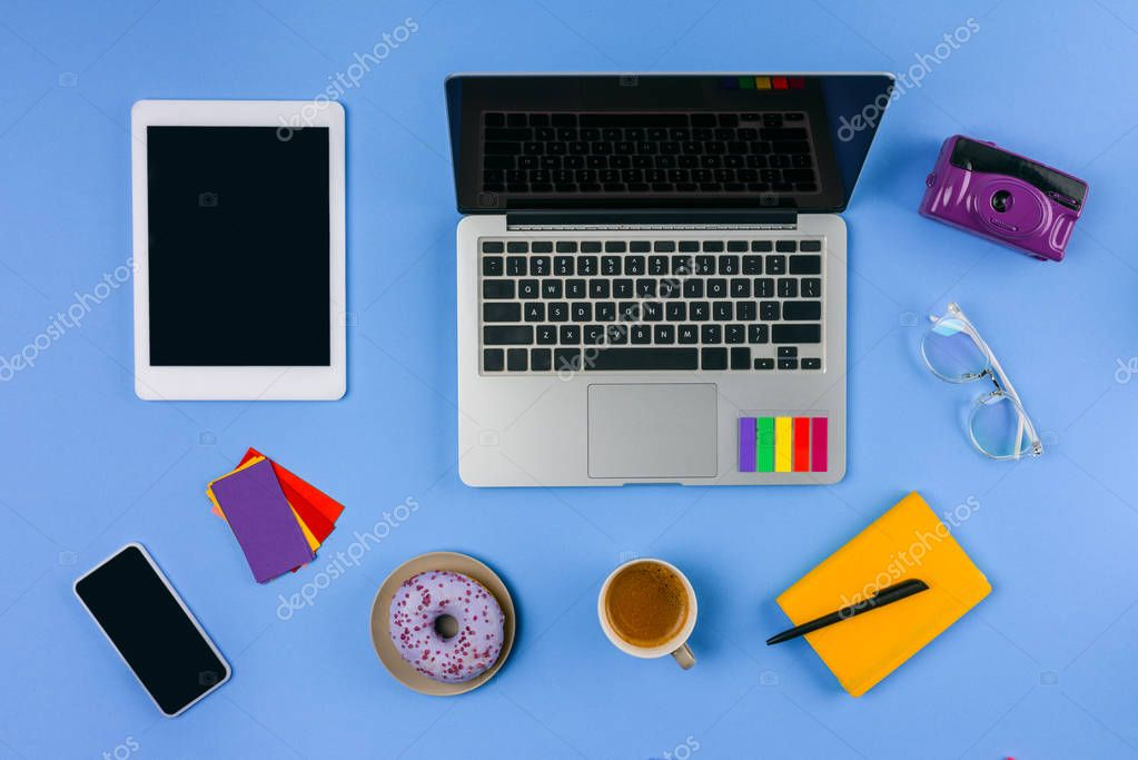 top view of laptop, digital tablet, smartphone, cup of coffee with doughnut and camera on blue