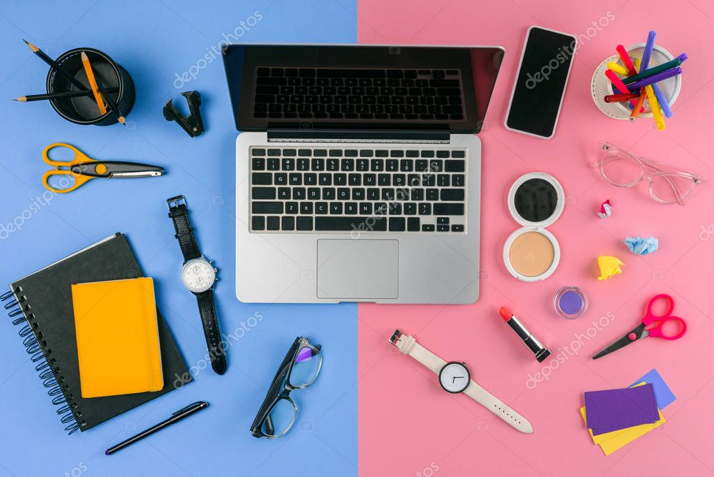 top view of laptop, smartphone and cosmetics with office supplies divided at male and female workplace