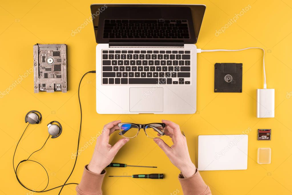 cropped shot of person holding eyeglasses while fixing laptop on yellow
