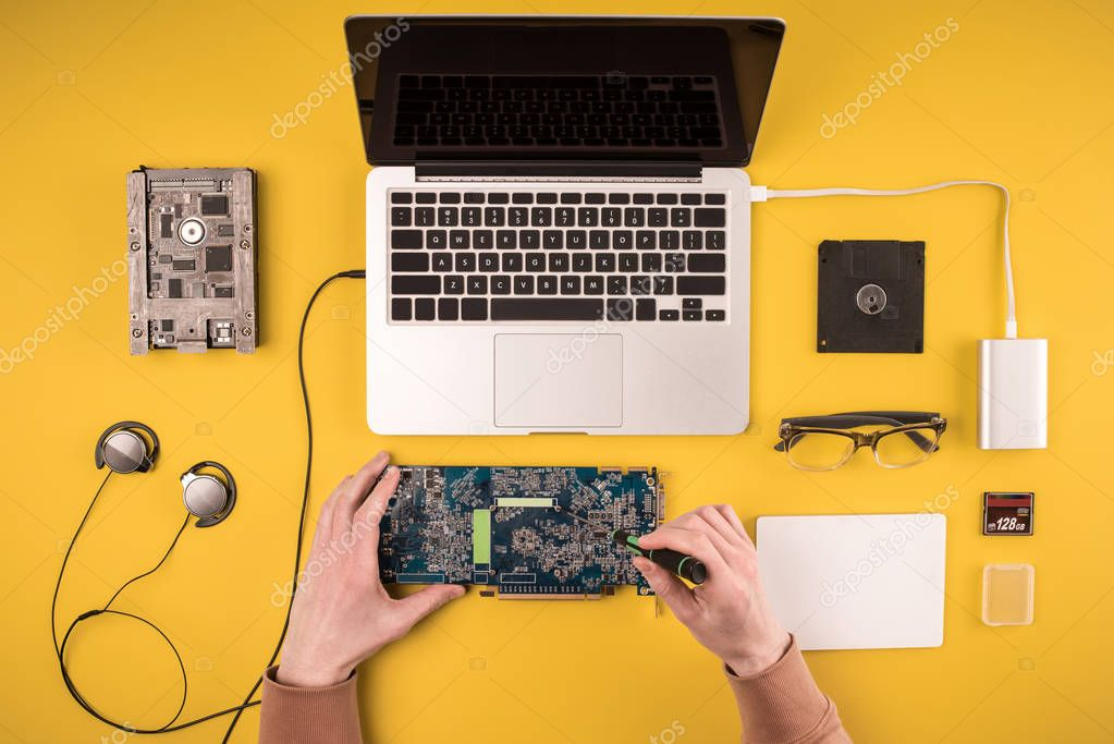 partial top view of person fixing laptop on yellow