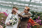 Fotografie stylish young groom in eyeglasses closing eyes to beautiful redhead bride with wedding bouquet