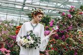 krásná elegantní mladá nevěsta drží svatební kytice a dotýká květiny v botanické zahradě