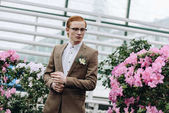 Photo handsome stylish young redhead groom in eyeglasses looking away in botanical garden