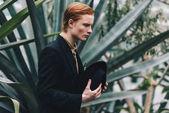 boční pohled na vážné mladá zrzka muž držel klobouk a koukal v botanické zahradě