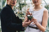 cropped shot of stylish young couple holding jewelry box with engagement ring