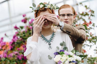 young man in eyeglasses closing eyes to beautiful redhead bride with wedding bouquet