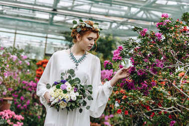 beautiful elegant young bride holding wedding bouquet and touching flowers in botanical garden