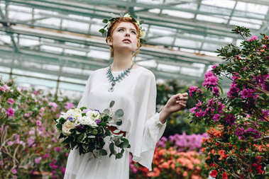 beautiful young woman in white dress and floral wreath holding wedding bouquet in botanical garden