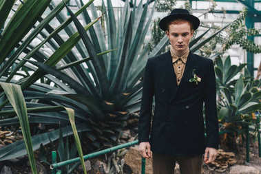 handsome stylish young groom in hat standing and looking down in botanical garden