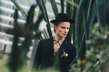 handsome young groom in hat looking away in botanical garden