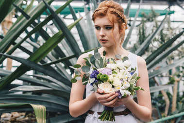 beautiful young redhead bride holding wedding bouquet and looking away in botanical garden