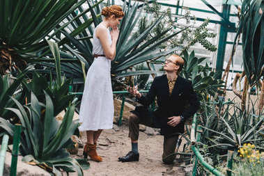 stylish young man standing on knee and making proposal to beautiful red-haired girl in botanical garden