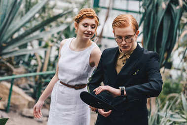 beautiful young redhead wedding couple looking at wristwatch in botanical garden
