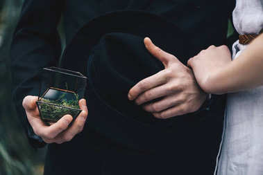 cropped shot of young couple standing together and man holding jewelry box with engagement ring