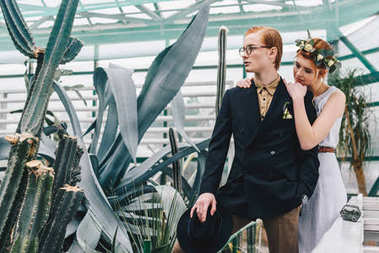 beautiful young redhead wedding couple standing together in botanical garden