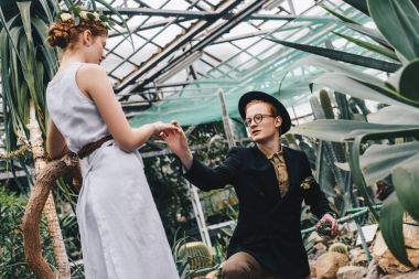 stylish young man in hat and eyeglasses making proposal to beautiful girl in botanical garden
