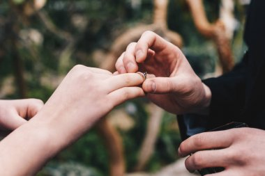 cropped shot of man putting wedding ring on finger of young bride