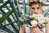krásná mladá zrzavá nevěsta drží svatební kytice a při pohledu na fotoaparát