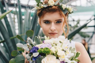 beautiful young bride in floral wreath holding wedding bouquet and looking at camera