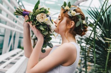 side view of beautiful young bride in floral wreath holding wedding bouquet