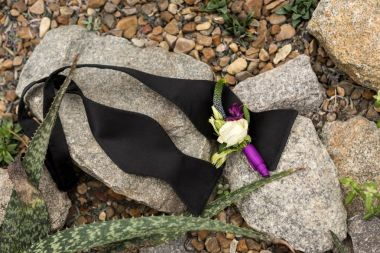 top view of beautiful boutonniere and untied black bow tie on stones