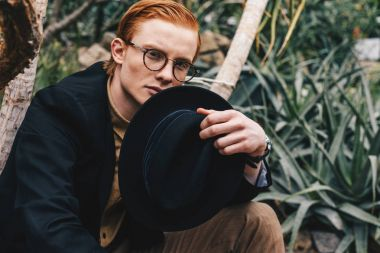 handsome young redhead man in eyeglasses holding hat and looking at camera