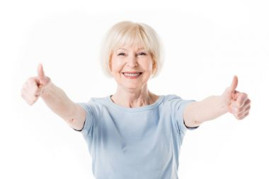 Smiling senior woman showing thumbs up isolated on white