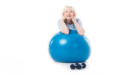 Smiling senior sportswoman with elbows on fitness ball and dumbbells on floor isolated on white