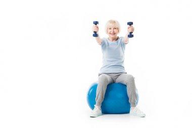 Smiling senior sportswoman holding dumbbells while sitting on fitness ball isolated on white
