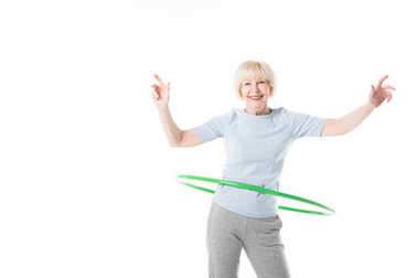 Smiling senior sportswoman doing hula hoop exercise isolated on white