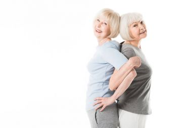Two senior sportswomen standing back to back while doing excercise isolated on white