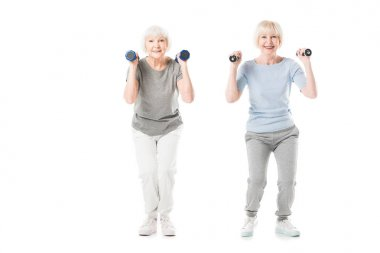 Smiling senior sportswomen doing exercise with dumbbells isolated on white