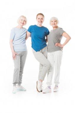 Three smiling sportswomen standing isolated on white