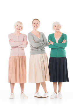 Three stylish women with crossed arms isolated on white