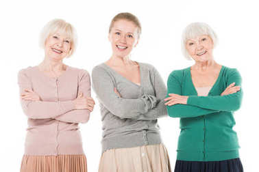 Portrait of three stylish women with crossed arms isolated on white