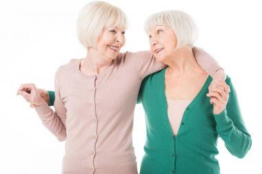 Two senior stylish women embracing isolated on white