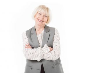 Portrait of smiling senior businesswoman with crossed arms isolated on white