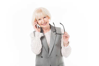 Smiling senior businesswoman talking on smartphone and holding eyeglasses isolated on white
