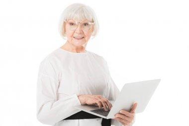 Stylish senior businesswoman in eyeglasses using laptop isolated on white