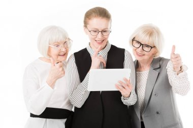 Three stylish businesswomen in eyeglasses looking at digital tablet isolated on white
