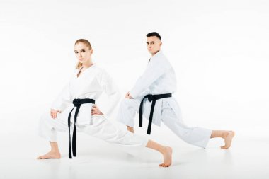 karate fighters stretching legs and looking at camera isolated on white
