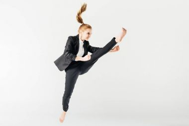 angry female karate fighter jumping and performing kick in suit isolated on grey