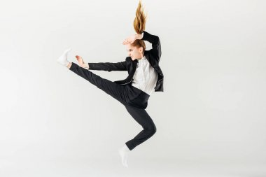 female karate fighter jumping and performing kick in suit isolated on grey