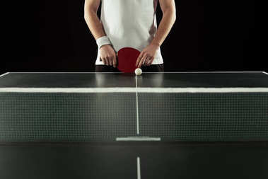 partial view of tennis player with racket standing at tennis table isolated on black